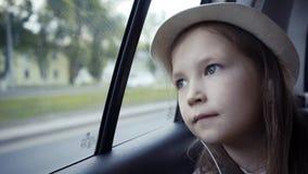 Маленькая девочка смотря вне от окна автомобиля на солнечном дне стоковое фото