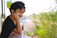 Маленькая девочка смотря вниз от балкона с улыбкой на ее стороне, Palande, Kokan Стоковое фото RF