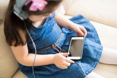 Маленькая девочка смотря кино шаржа на сотовом телефоне Стоковое фото RF