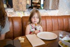 Маленькая девочка смотря croquette в вилке на ресторане Стоковые Изображения