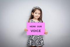 Маленькая девочка со знаком услышать наш голос стоковое изображение