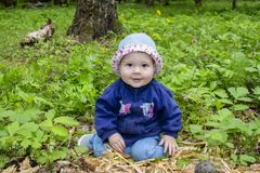 Маленькая девочка со свитером и шляпой сидит в середине леса и взглядов в камеру Счастливая девушка учит мир, стоковые фотографии rf