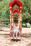 Маленькая девочка сползает на спортивную площадку стоковое фото rf