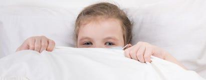 Маленькая девочка спрятала в кровати в медицинской маске, для того чтобы защитить от инфекции стоковые изображения rf