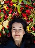 Маленькая девочка среди листьев и цветков стоковое фото