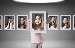 Маленькая девочка среди серий ее портретов стоковая фотография