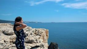 Маленькая девочка стоит на краю скалы и взглядов на море Красивая девушка наслаждаясь взглядом на скале над морем стоковая фотография