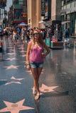 Маленькая девочка стоя на прогулке Голливуда славы стоковая фотография