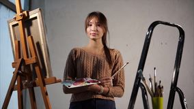 Маленькая девочка студент художественного училища, стоя в workroom во времени вечера видеоматериал