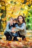 Маленькая девочка с более старым братом и их мама играя в осени паркуют стоковая фотография rf