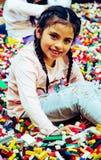 Маленькая девочка с воспитательными блоками игрушки Игра детей на амбулаторном учреждении или preschool Беспорядок в комнате дете стоковое изображение rf