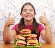 Маленькая девочка с гамбургерами и большими пальцами руки вверх Стоковые Изображения RF