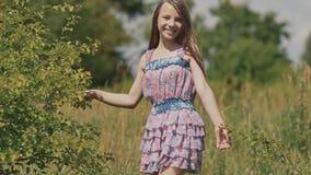 Маленькая девочка с длинной прогулкой волос на луге лето дня теплое видеоматериал
