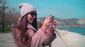 Маленькая девочка с длинными волосами в стеклах, шляпе и пальто на обв акции видеоматериалы