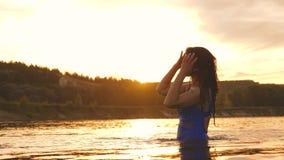 Маленькая девочка с длинными волосами купает и брызгает воду на заходе солнца Счастливая и смеясь женщина охлаждает в реке o видеоматериал