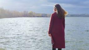 Маленькая девочка с ее волосами стоит около воды в холодном сезоне задний взгляд Молодая женщина стоя около озера стоковое изображение rf