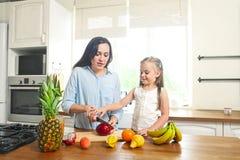 Маленькая девочка с ее матерью в кухне подготавливая свежий fru стоковая фотография rf