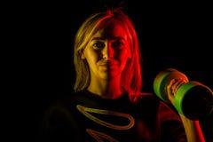 Маленькая девочка с зелеными гантелями в ее руках в срок для спорт и разминок с бортовым освещением желтого и красного на черноте стоковое изображение