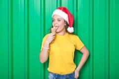 Маленькая девочка с конусом мороженого и шляпа Санта Клауса против зеленой стены Принципиальная схема рождества стоковое фото rf