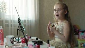 Маленькая девочка с красными волосами брызгает духи или воду туалета, взгляды в зеркале, макияж, сторону, моду, стиль видеоматериал