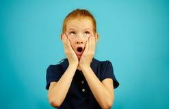 Маленькая девочка с красными волосами в панике кладет ее руки для того чтобы смотреть на, раскрытый рот и смотрит вверх, выражает стоковая фотография