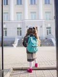 Маленькая девочка с красными кабелями идет к школе, взгляду от задней части Стоковое фото RF
