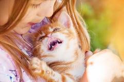 Маленькая девочка с красным котенком в руках закрывает вверх BESTFRIENDS I Стоковые Фотографии RF