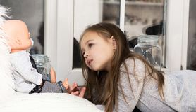 Маленькая девочка с куклой на предпосылке окна стоковое изображение