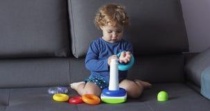 Маленькая девочка с курчавыми играми светлых волос с головоломкой забавляется голубые одежды Смотрит сконцентрированный акции видеоматериалы