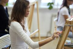 Маленькая девочка с курчавыми каштановыми волосами одетыми в белой блузке рисует изображение с карандашем в рисуя школе стоковая фотография rf