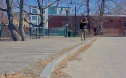 Маленькая девочка с курчавыми красными волосами идя прогулка доски в предыдущей весне Стоковые Фото