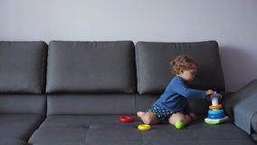 Маленькая девочка с курчавыми светлыми волосами играет с воспитательными игрушками голубые одежды чувствует счастливой акции видеоматериалы