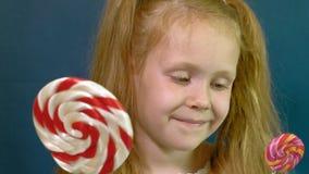 Маленькая девочка с леденцом на палочке на голубой предпосылке r акции видеоматериалы