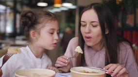 Маленькая девочка с мамой ест горячие вареники в ресторане Дуновения мамы на варенике, который нужно охладить его акции видеоматериалы