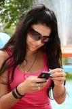 Маленькая девочка с мобильным телефоном в парке th стоковые фото