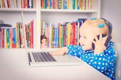 Маленькая девочка с наушниками и компьтер-книжкой стоковое изображение rf
