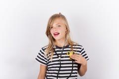 Маленькая девочка с обтекателем втулки непоседы как стетоскоп - концепция здоровья стоковые фото