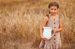 Маленькая девочка с опарником молока в counrtyside стоковые изображения