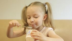 Маленькая девочка с отрезками провода есть йогурт, полезные молочные продучты для детского питания сток-видео