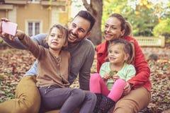 Маленькая девочка с отцами помогает принять автопортрет на телефоне Стоковое Изображение RF