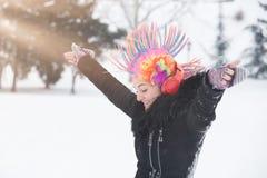 Маленькая девочка с париком клоуна красочным и наушники на день снега стоковая фотография rf