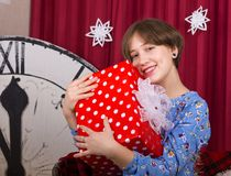 Маленькая девочка с подарочной коробкой на предпосылке часов Нового Года стоковые фото