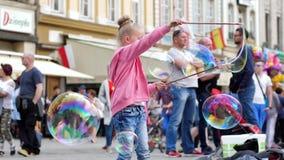 Маленькая девочка с пузырями мыла тратя время на пешеходной улице в городе