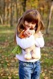 Маленькая девочка с собакой игрушечного в пуще осени Стоковая Фотография RF