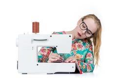 Маленькая девочка с стеклами шьет на швейной машине, изолированной на белой предпосылке стоковые фото
