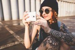 Маленькая девочка с татуировками и dreadlocks в голубой крышке использует smartphone на фоне бетонной стены стоковое изображение rf