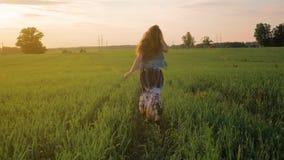 Маленькая девочка с улыбкой с прямыми волосами, в длинном платье бежит вдоль зеленого поля Заходящее солнце движение медленное акции видеоматериалы