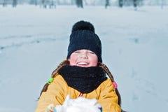 Маленькая девочка с усмехаться отрезков провода счастливый ребенок держа вне снег портрет зимы ребенк стоковое фото