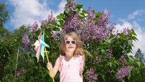 Маленькая девочка с pinwheel в парке рядом с зацветая сиренью весной сток-видео
