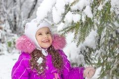 Маленькая девочка тряся ветвь сосны покрытую снегом Стоковое Фото